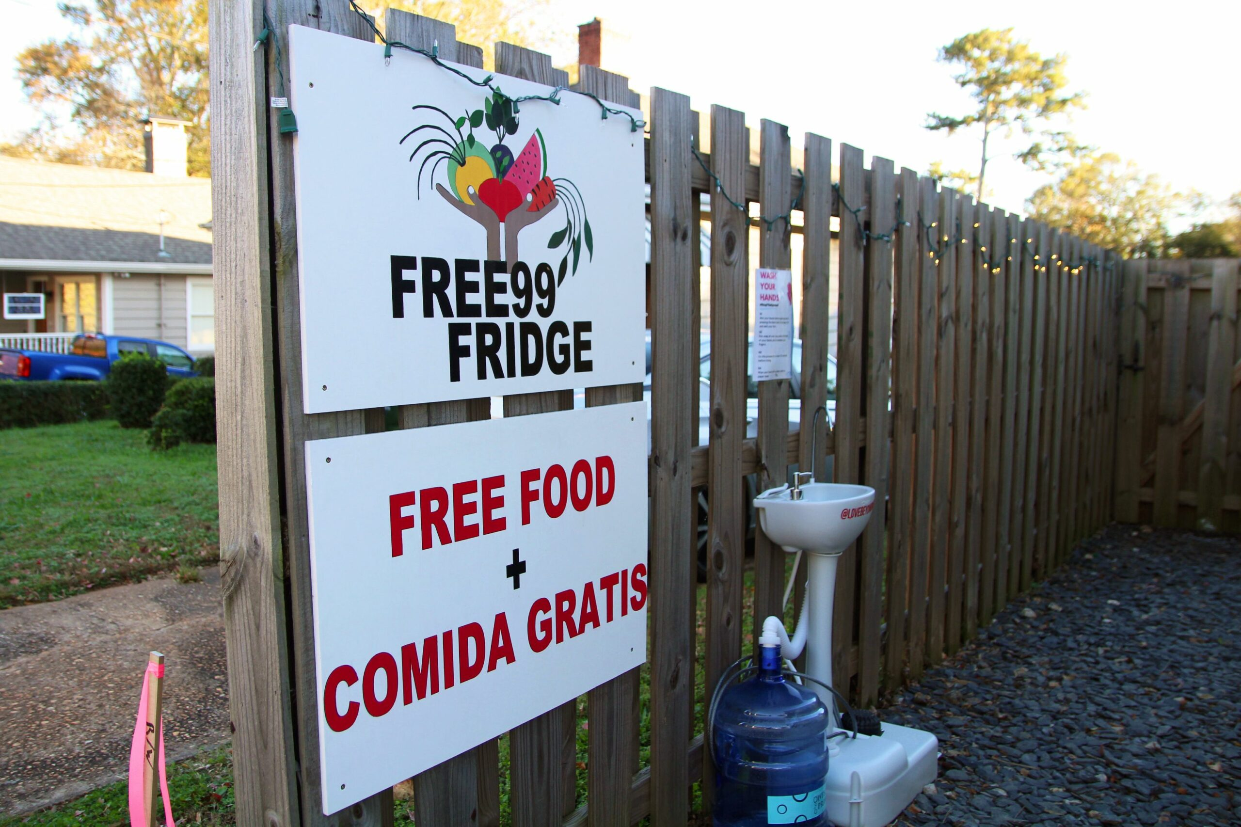 "A fence picture of the Free99Fridge logo, with a sign that says ""FREE FOOD + COMIDA GRATIS"" with a public sink in the background"