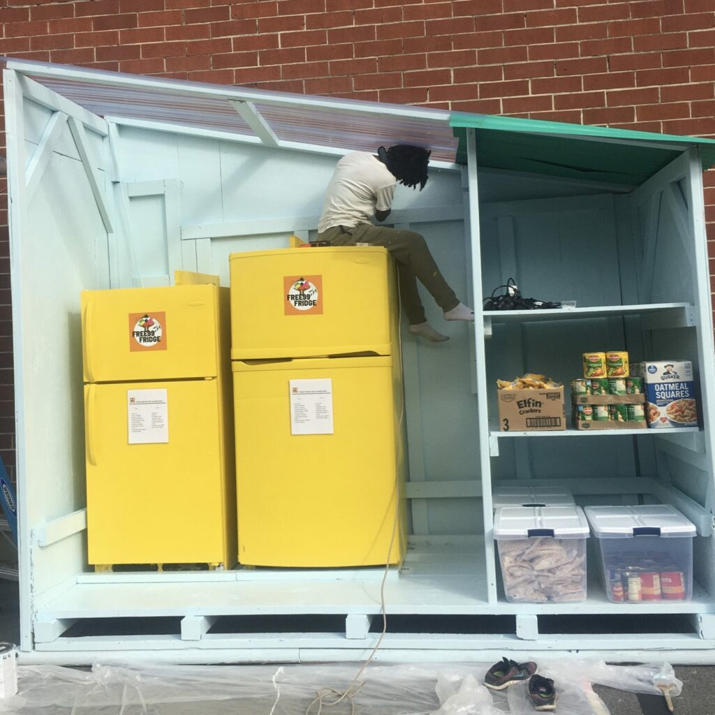 The two fridges from the previous picture are seen. A person is sitting on top of them, adjusting the roof. They are preparing an outdoor shelter for the fridges in preparation for use outdoors.