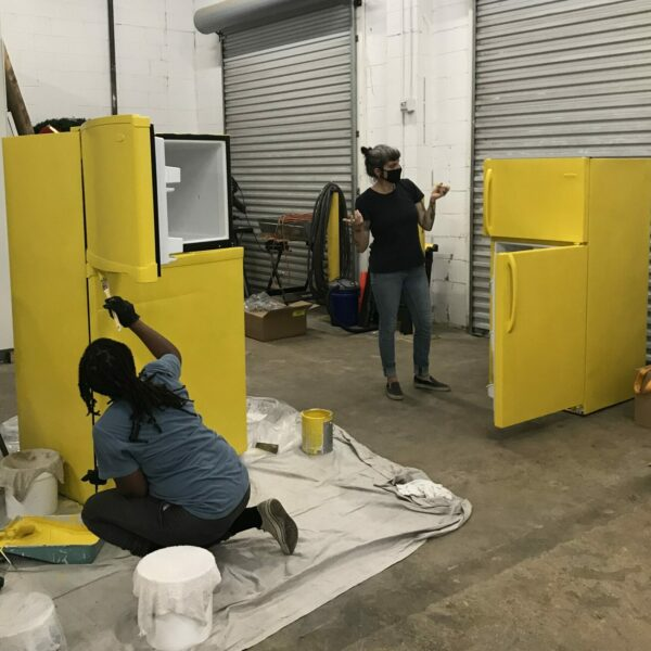Two people are in a warehouse painting a pair of fridges bright yellow.