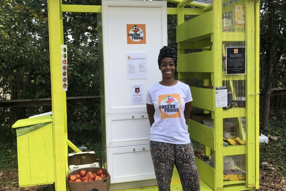 Latisha Springer stands proudly in front of one of the community fridges. She is wearing colorful leggings and a Free99 shirt.