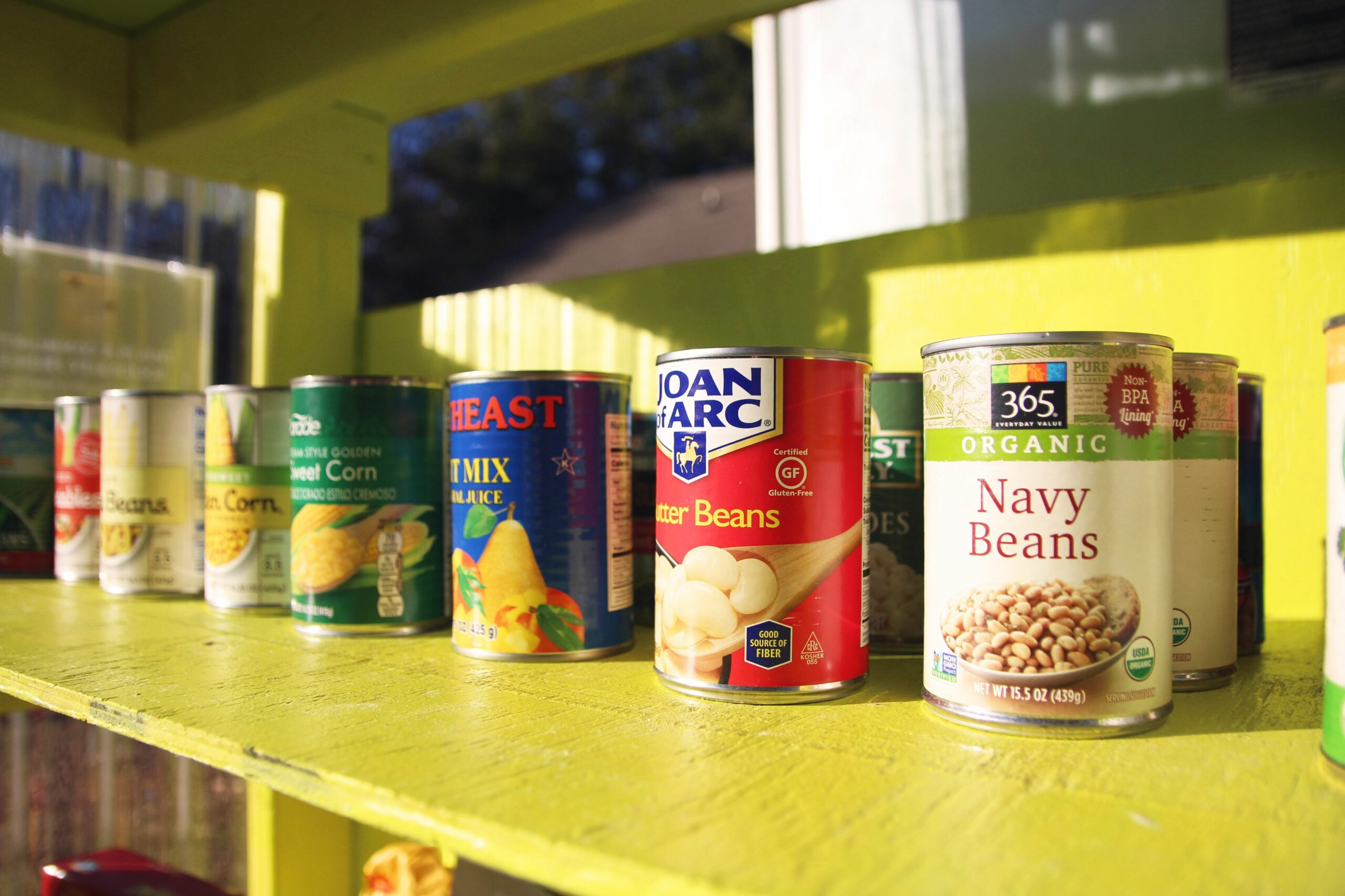 A neat set of canned foods sits in a pantry. There are Navy beans, buttoer beans, and sweet corn visible.